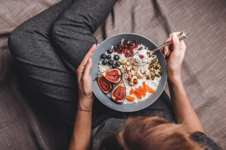 Woman in home clothes eating vegan Rice coconut porridge with figs, berries, nuts. Healthy breakfast ingredients. Clean eating, vegan food concept
