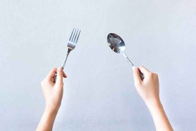 Woman hands isolated showing two hands holding spoon and fork on grey background, gesture of eating dinning.