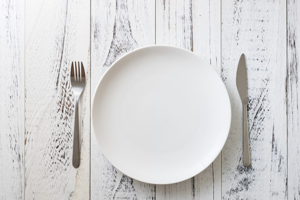 Round Plate with utensils on white wooden table background