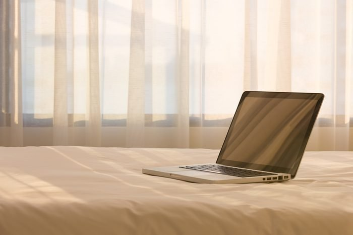 Working in bed , laptop on white bed with white curtain in the background with selective focus.
