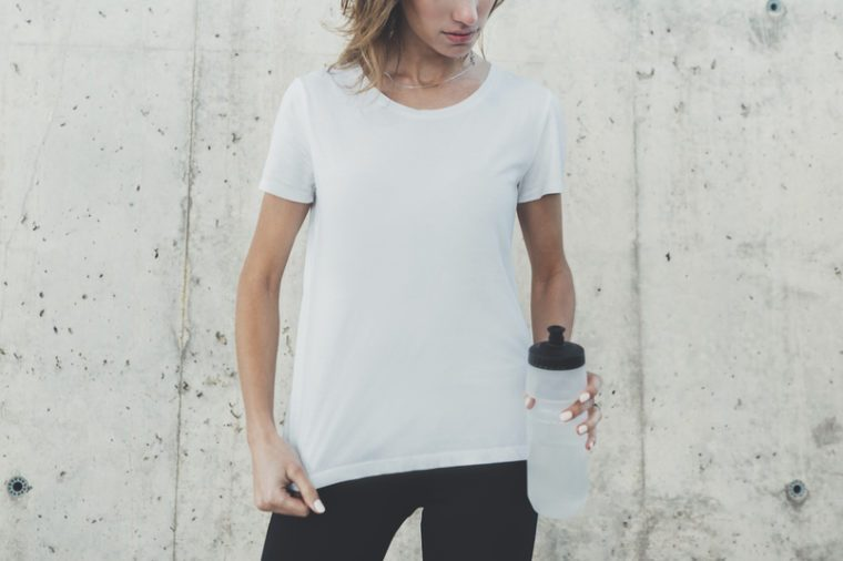 Horizontal image of young pretty girl wearing white blank t-shirt with copy space for your design or logo, hipster girl holding blank bottle of water and wearing template t-shirt, mock-up of t-shirt