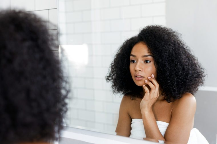 Attractive young woman touching her face, inspecting skin in front of the bathroom mirror