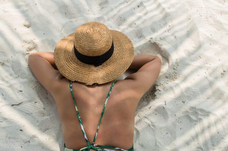 beautiful girl in green bikini on the white sand maldivian palm beach, top view, model view