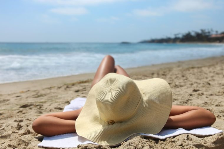 Beautiful Woman Laying Out Sunbathing at the Beach Wearing a Hat
