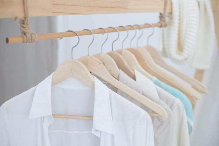 White shirts hanging on white built-in cloths racks