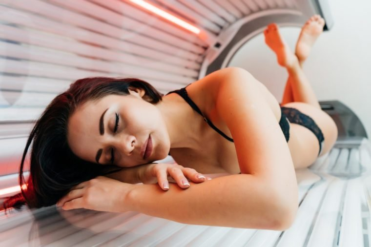 young brunette girl lies in a sunroom, sunbathing under ultraviolet rays