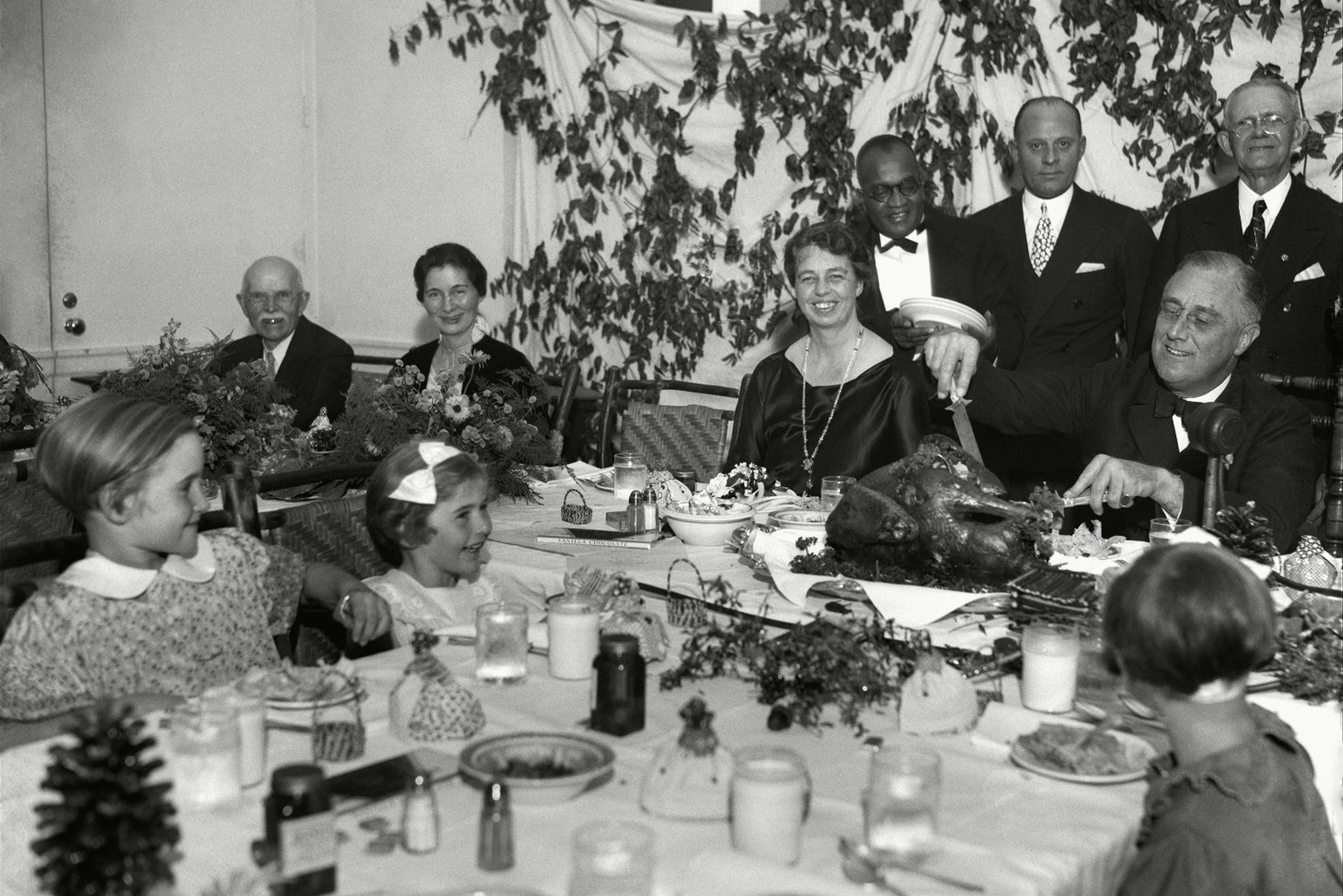 Mandatory Credit: Photo by AP/Shutterstock (6003359a) President Franklin D. Roosevelt carves the turkey during the annual Thanksgiving dinner for polio patients at Warm Springs, Ga., with first lady Eleanor Roosevelt smiling beside him FDR Carves Turkey 1933, Warm Springs, USA