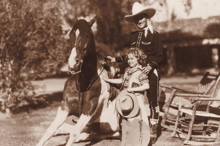 Hollywood cowgirl Shirley Temple with Monty Montana, c. 1938, movie star Shirley Temple and roping celebrity Monty Montana gave a short roping performance at a Western theme party at the Desert Inn in Palm Springs, California in 1938