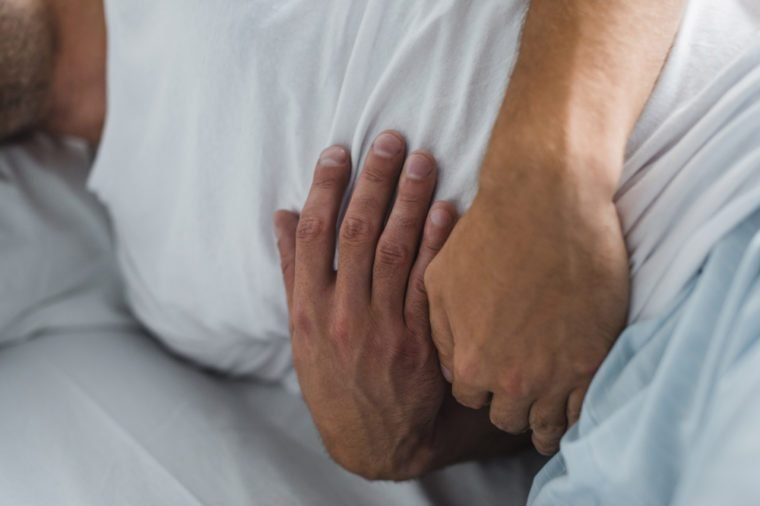 close-up partial view of man suffering from stomach pain in bed