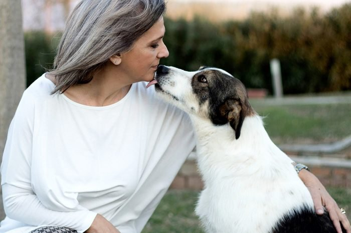 Senior woman kissing her dog outside her home.