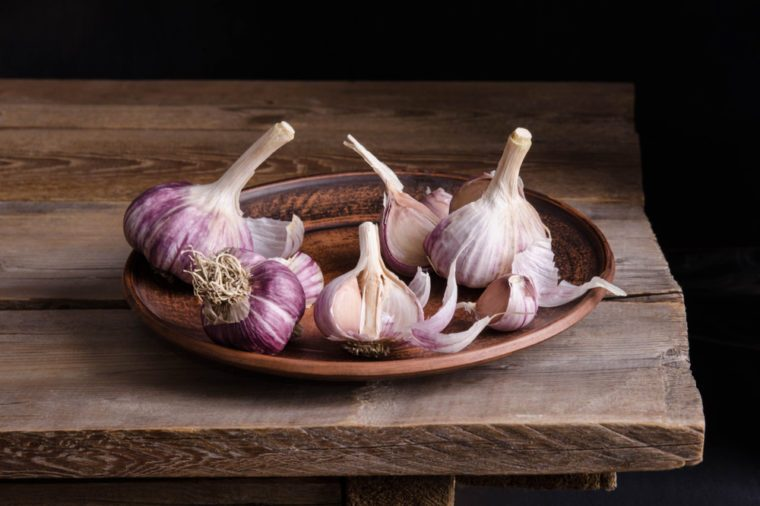 garlic in the plate on old wooden table and black background