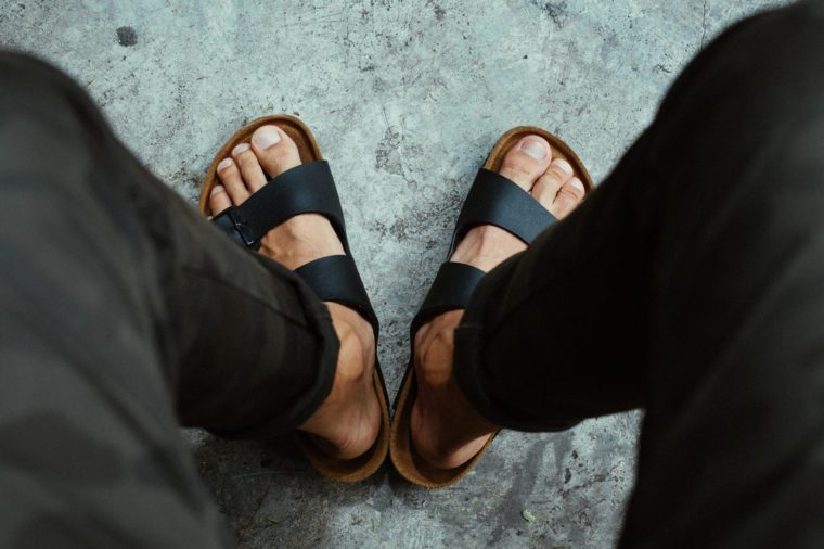 Male feet and sandals selective focus and high contrast