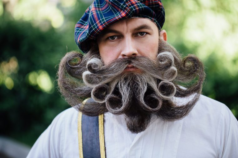 Close-up portrait of a brave Scot with a amazing beard and mustache curls . Checkered red Scottish kilt skirt, hat with pompon, cane and sword. Beard styling by professional barbershop.