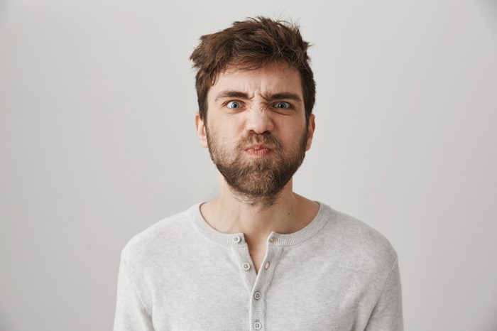 Portrait of funny weird guy with messy hair and beard making faces, puckering eyebrows and sulking, standing over gray background with offended or irritated expression, losing his temper