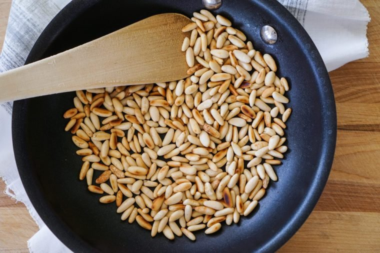 toasted pine nuts in skillet/pan on wood background