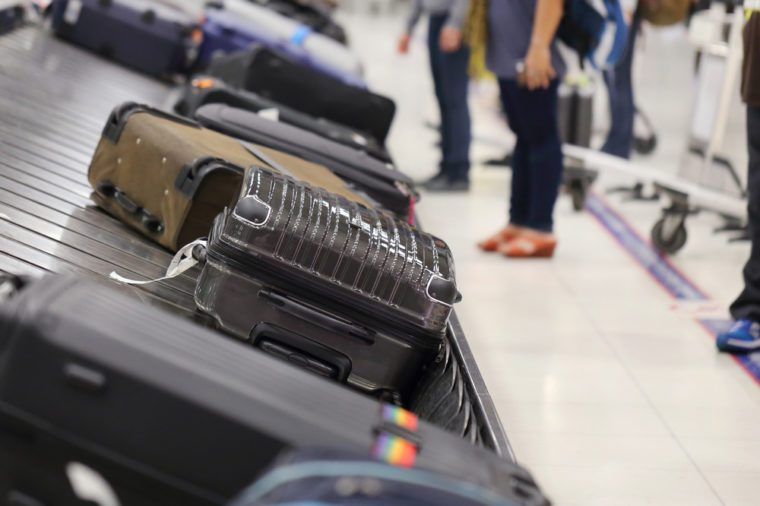 image of people picking up suitcase on luggage conveyor belt in the airport
