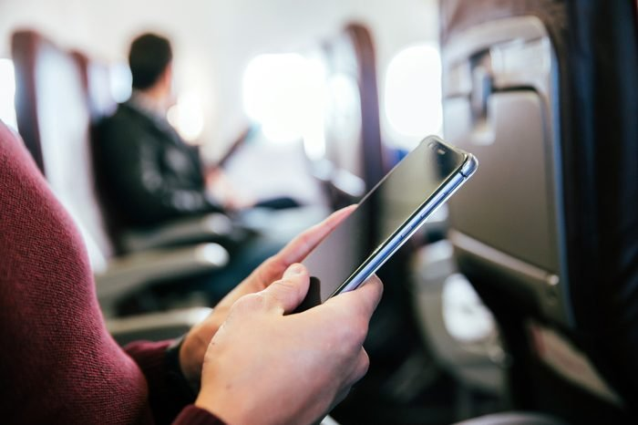 Man using a smartphone in an aircraft.