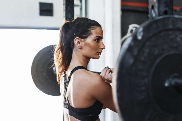 Portrait of muscular young woman standing at gym with barbell