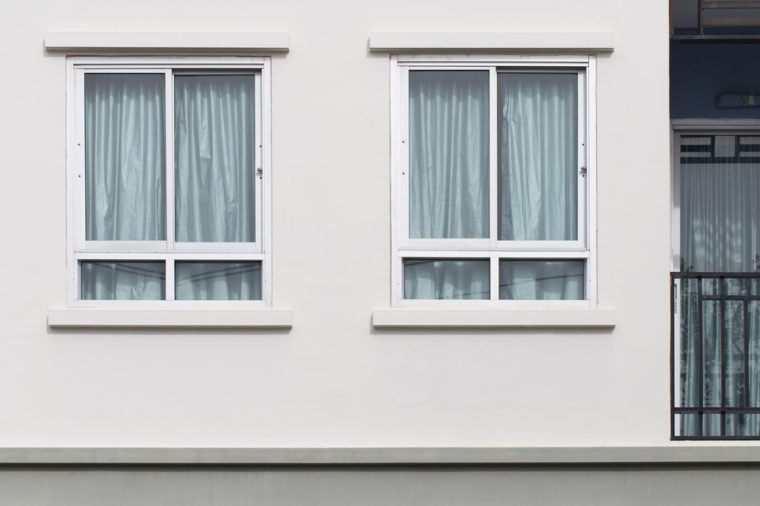 Two modern windows with uv protection curtain on white wall, outdoor view