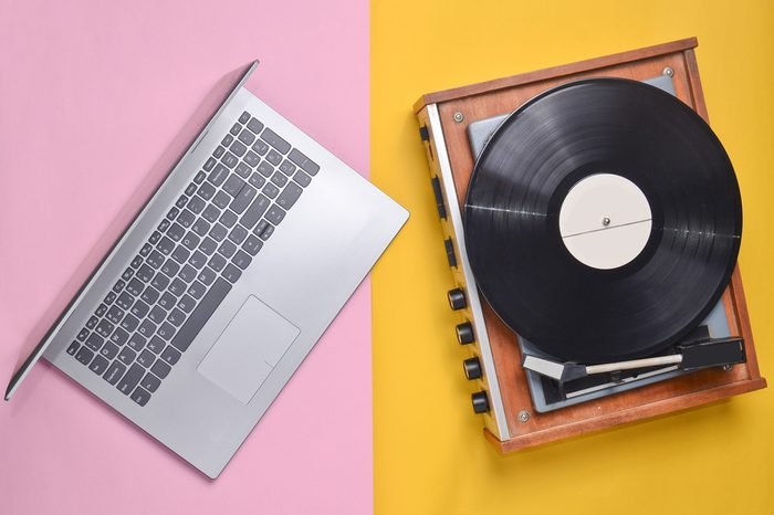 Laptop, vinyl player on a colored pastel background. Modern and outdated technology, top view