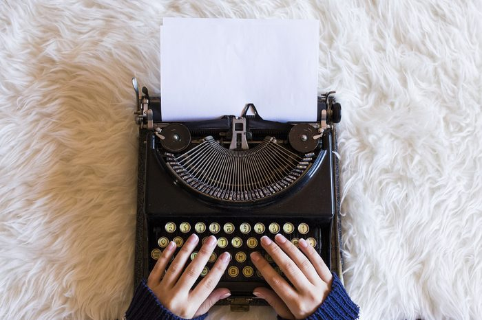 Close up of female hands typing on retro typewriter. Cup of coffee is at right side. Top view. Indoors. white background
