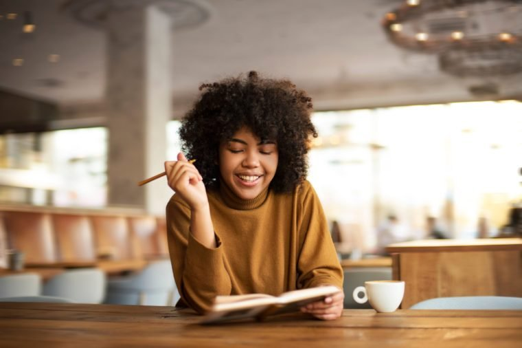 A young girl of African-American appearance sits at a table. She has a coffee break in a warm uninhabited atmosphere. She talks on the phone with her friends, has a rest and drinks tasty coffee