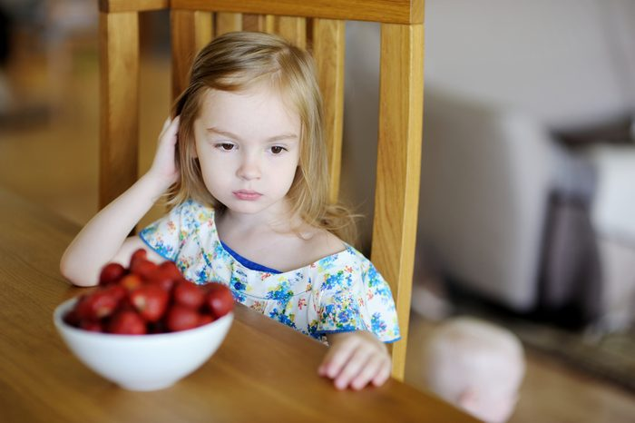 Thoughtful girl sitting next to fresh strawberries in a bowl
