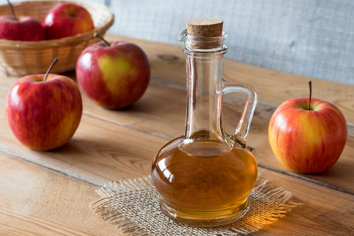 A bottle of apple cider vinegar on a wooden table, with apples in the background