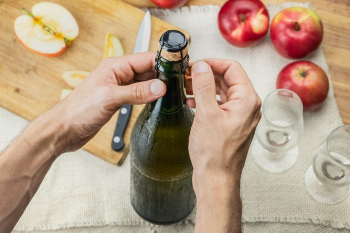 Top view of male hands opening bottle of premium cidre. Shot from above of uncorking beautiful ice cold bottle of apple wine, locally grown ripe apples in background