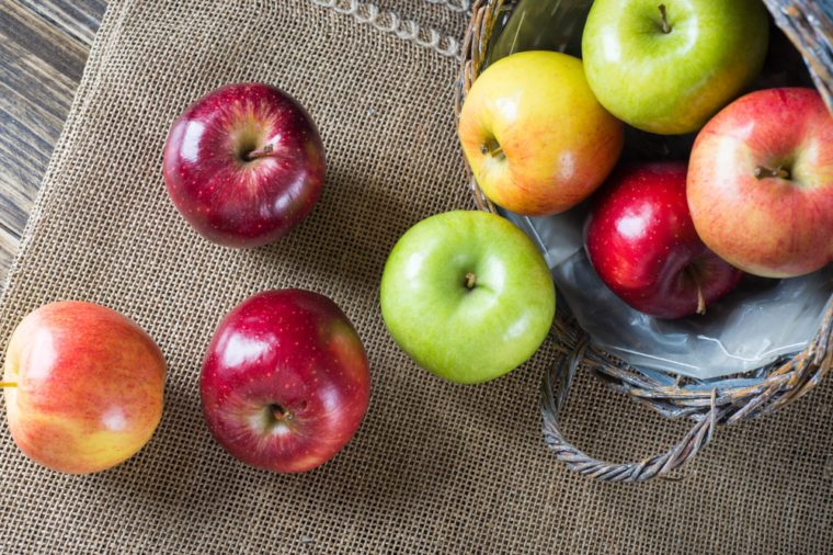 Apples in a basket on burlap and wooden background, view from the top