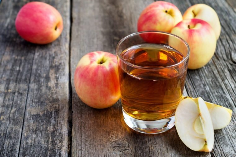 apple juice in a glass and apples on wooden background