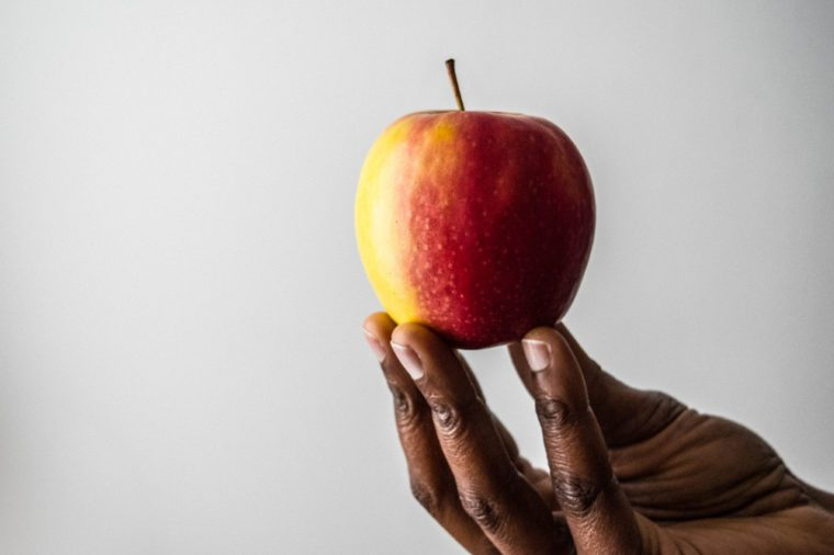 African American Woman's hand and fingers holding red pink lady apple fruit isolated on a white background in fresh and juicy color. Food and dieting concept.