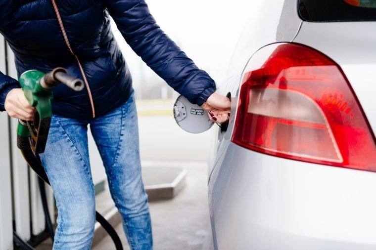 Woman opening fuel filler at the gasoline station