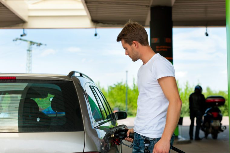 Refuel the car on a gas station; man holding the tap