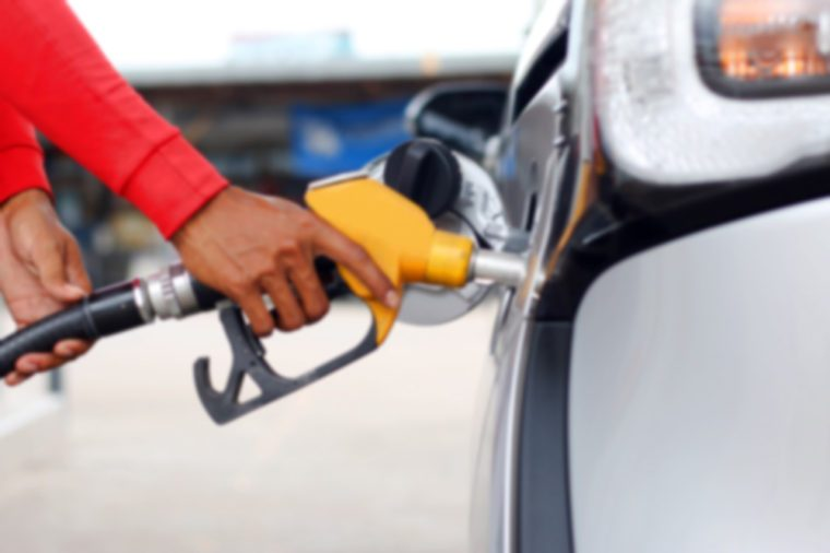 blur of hands fills up his car with a gasoline at gas station