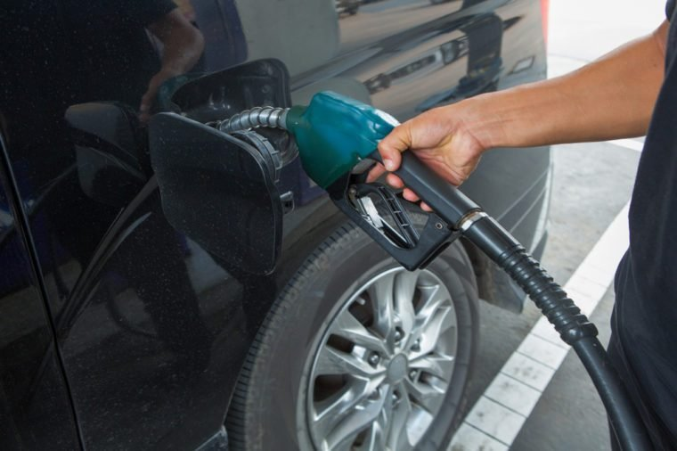 Man refueling black car with gasoline at gas station.