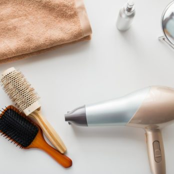 hair tools, beauty and hairdressing concept - hairdryer, brushes, mirror and towel on white background