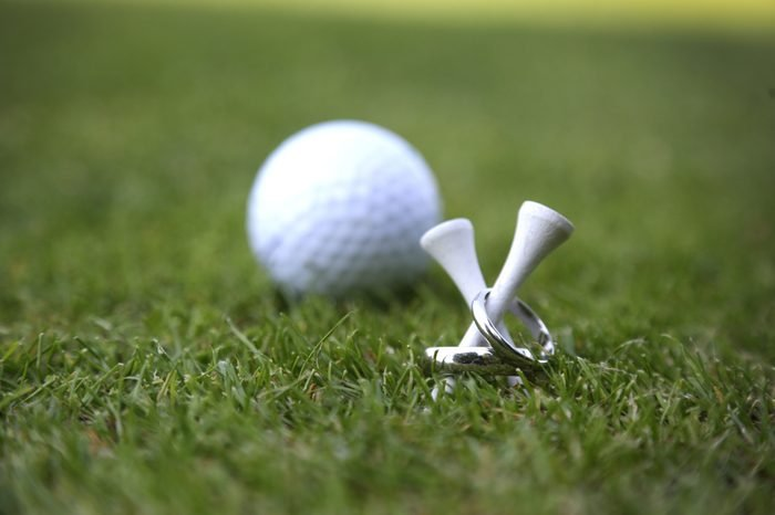 Wedding rings on golf tees photo with golfball in the background