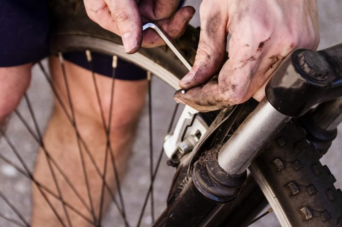Man with his hands dirt of grease is fixing a bike