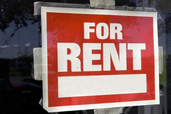 Red and white For Rent Sign taped to inside of window. Horizontal.