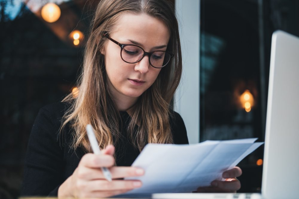 Portrait of a young beautiful girl sitting at table with laptop, holding pen in hand  and reading piece of paper. Education concept