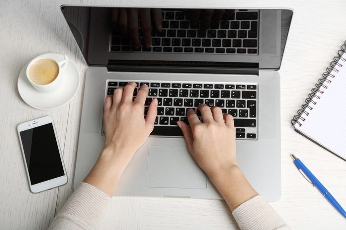 Woman working with laptop placed on wooden desk. Top view