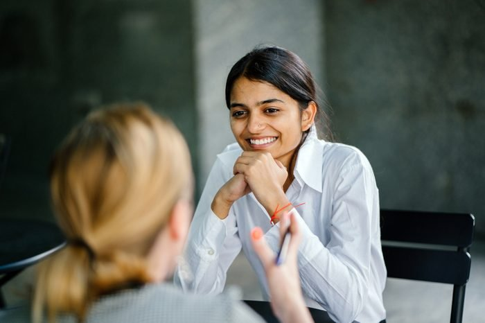 A young and attractive Indian Asian woman is interviewing for a job. She is dressed professionally in a white shirt and is sitting and talking to her interviewers. She is confident and relaxed.