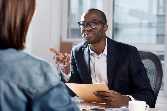 I listen to your suggestions. Portrait of confident qualified young manager is sitting with his colleague female at table. He is looking at her attentively and gesticulating