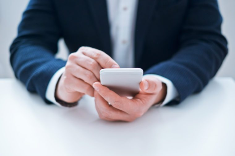 Man's hands using mobile phone sitting in the office. Close-up image