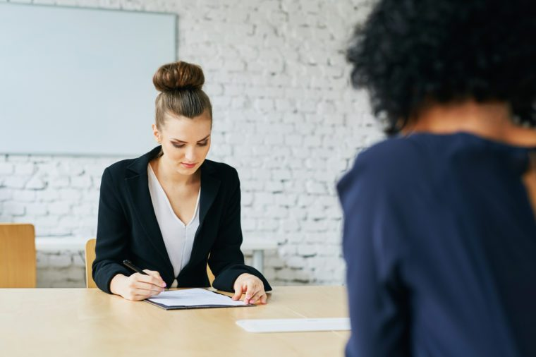 Job interview - young woman signing employment contract