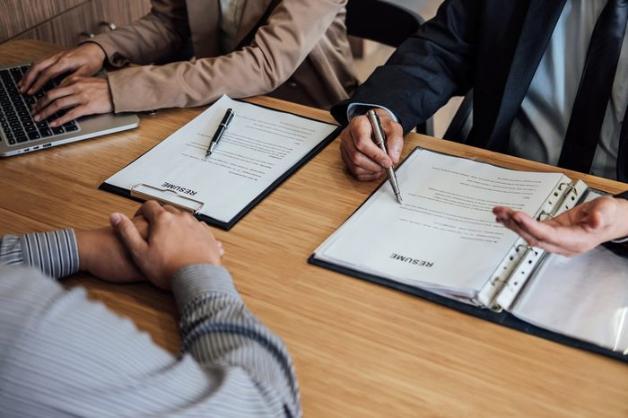 Two senior manager reading a resume during a job interview, Employer interviewing to ask young male job seeker for recruitment talking in office.
