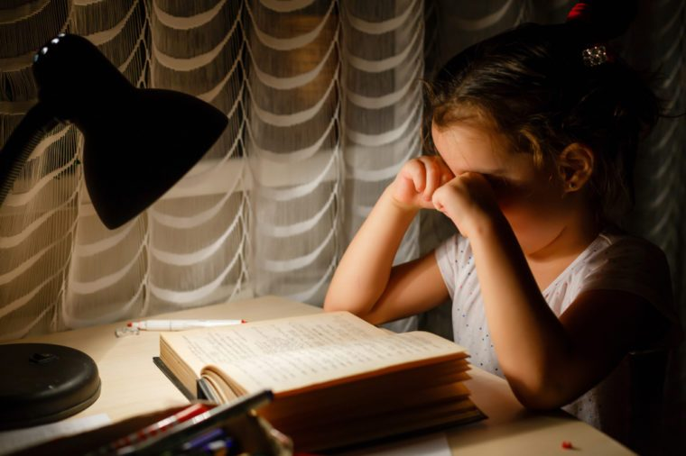 Beauty attractive little girl looking at all homework feeling bored and unhappy when she preparing