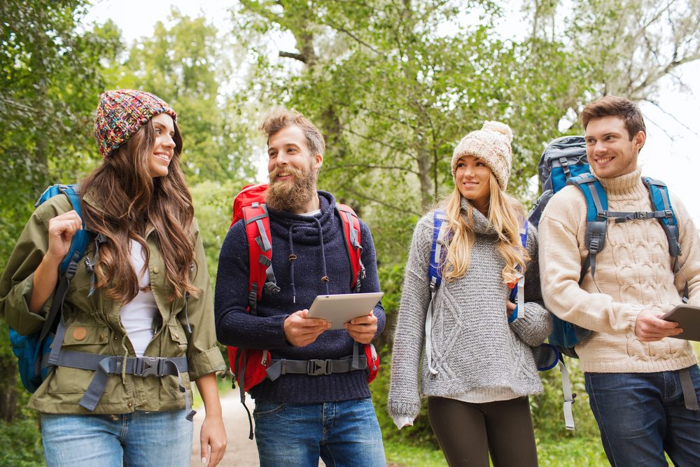 adventure, travel, tourism, hike and people concept - group of smiling friends with backpacks and tablet pc computer walking outdoors