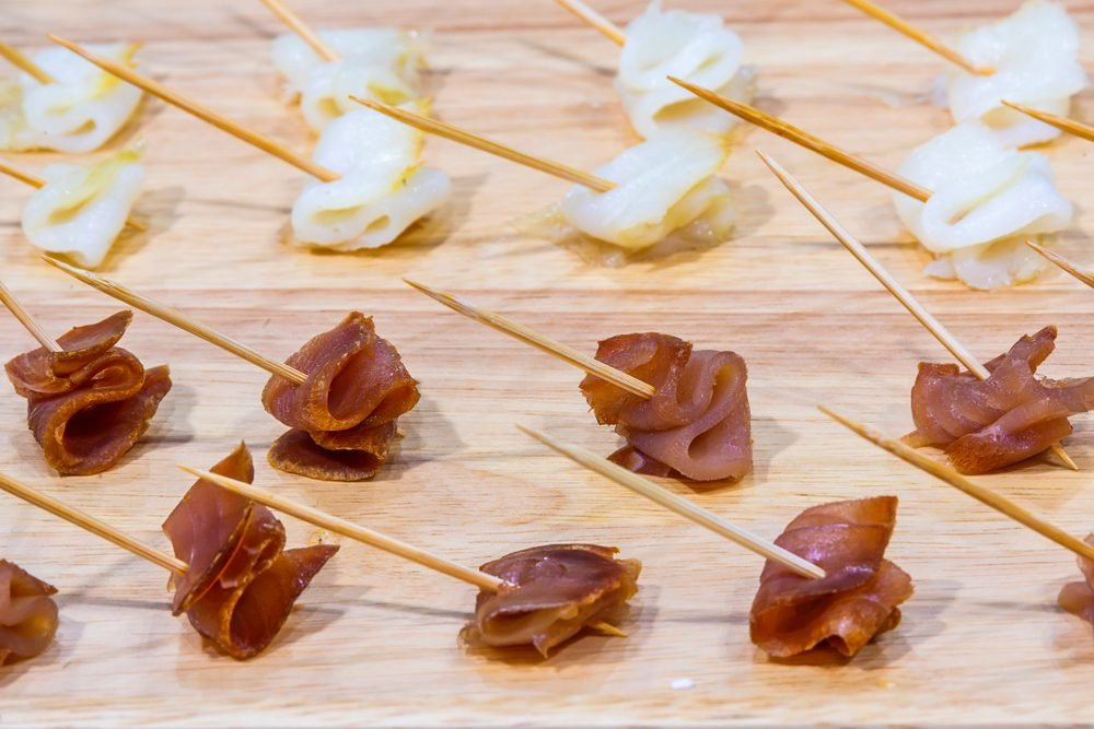Advertising, Business, Food, Health Concept - Offering food samples to customers in shop. Smoked tuna on a wooden stick. Select focus